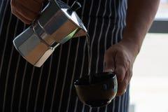 Человек лить горячий кофе в чашку Стоковое Изображение