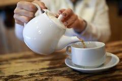 Человек лить черный чай стоковое фото rf
