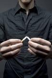 Человек ломает сигарету Стоковые Фотографии RF