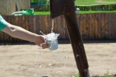 Человек льет чашку воды от столбца (кран) стоковая фотография