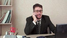 Человек менеджера офиса с бородой и стекла говоря счастливо на смартфоне акции видеоматериалы