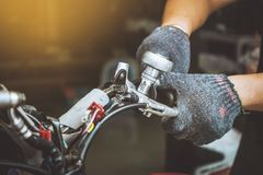 Человек механика используя ключ для того чтобы отремонтировать или обслуживать мотоцикл на стоковые фотографии rf