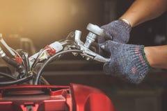 Человек механика используя ключ для того чтобы отремонтировать или обслуживать мотоцикл на стоковая фотография rf