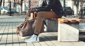 Человек моды элегантный африканский с сумкой сидит на стенде стоковое фото rf