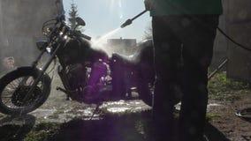 Человек моет мотоцикл с высоким уборщиком давления сток-видео