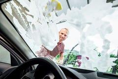 Человек моет стекло окна автомобиля, внутри взгляда камеры автомобиля Стоковое Изображение RF