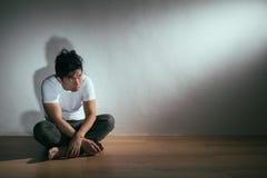 Человек молодого аутизма терпеливый сидя на деревянном поле Стоковое фото RF
