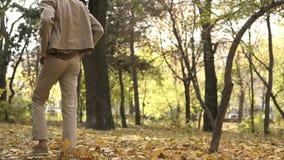 Человек молодого streetstyle случайный в солнечных очках идя в парк осени и пнуть кучи желтых кленовых листов видеоматериал