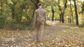 Человек молодого streetstyle случайный в солнечных очках идя в парк осени и пнуть кучи желтых кленовых листов сток-видео