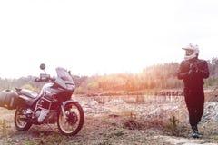 Человек мотоциклиста стоит с его мотоциклом приключения С дороги Отключение мотоцикла enduro путешествуя, спорт перемещения образ стоковая фотография