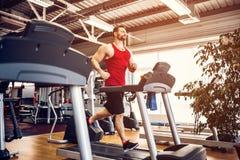 Человек мышцы бежать на третбане стоковое фото rf