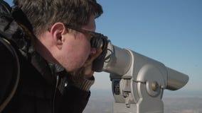 Человек наблюдает в touristic телескопе в горах сток-видео