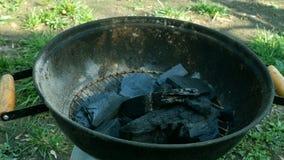 Человек наводит уголь в гриле металла или барбекю для гореть на открытом воздухе на солнечный летний день акции видеоматериалы