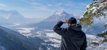 Человек наслаждается взглядом и смотрится вниз на Garmisch-Partenkirchen и Farchant стоковые изображения rf