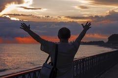 Человек наслаждается заходом солнца на море стоковая фотография rf