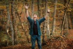 Человек наслаждается листьями падая от деревьев стоковое фото