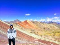 Человек наслаждаясь взглядом неимоверных выходов гор радуги стоковое фото rf