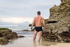 Человек наслаждаясь видом на океан bali Индонесия Стоковое фото RF
