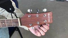 Человек настраивает настраивая колышки на гитаре Martinez на серой предпосылке акции видеоматериалы