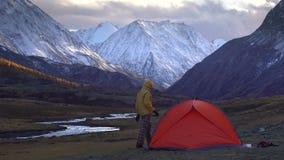 Человек настраивает шатер на предпосылке ландшафта горы 4K акции видеоматериалы