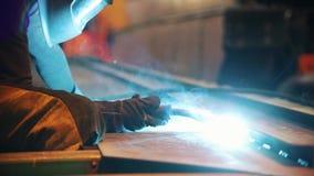 Человек начинает работу со сварочным аппаратом Сваривать длинного элемента металла видеоматериал