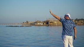 Человек на береге показывает что-то вручную к людям на яхте на море человек на пляже развевая его оружия залив моря видеоматериал