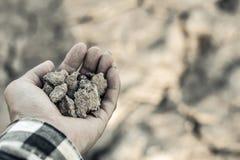 Человек на засух-пораженной земле в надежде на брать стоковая фотография