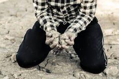 Человек на засух-пораженной земле в надежде на брать стоковое фото rf