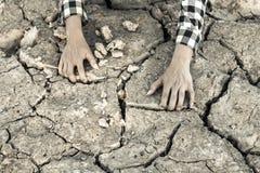 Человек на засух-пораженной земле в надежде на брать стоковая фотография rf