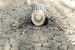 Человек на засух-пораженной земле в надежде на брать стоковое фото