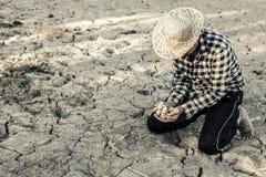 Человек на засух-пораженной земле в надежде на брать стоковые изображения rf