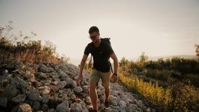 Человек на заходе солнца поднимает к горе с рюкзаком сток-видео