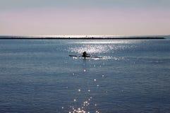 Человек на каяке в голубом море на восходе солнца в Италии стоковое изображение