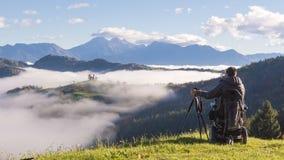 Человек на кресло-коляске принимая фото красивого ландшафта в туманном утре, St. Thomas Словению стоковая фотография rf
