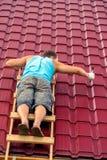 Человек на лестницах с ремонтами молотка заволакивание крыши стоковые изображения rf