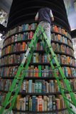 Человек на лестнице заполняя башню полок с книгами стоковое изображение