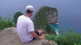 Человек на скале на заливе Manta или пляже Kelingking, острове Nusa Penida, Индонезии видеоматериал