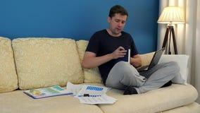Человек на софе с компьтер-книжкой пишет на блокноте домашняя работа видеоматериал
