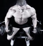 Человек на стенде с весами штанги в тренировке рук стоковая фотография rf