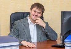 Человек на столе в офисе усмехаясь счастливо стоковые фотографии rf