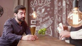 Человек на счетчике бара пробует пиво и одобряет хороший вкус акции видеоматериалы