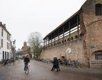 Человек на улице велосипеда и людей пересекая в старом городе zwolle в нидерландской близко стене древнего города Стоковые Фото