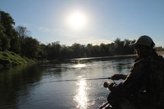 Человек на усаживании и рыбной ловле рыбацкой лодки утра стоковое изображение rf