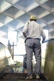Человек на эскалаторе в центре или подполье торгового центра стоковые фото