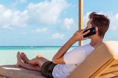 Человек на sunchair в тропическом положении вызывая друзей со смартфоном Ясная вода бирюзы как предпосылка стоковые фотографии rf