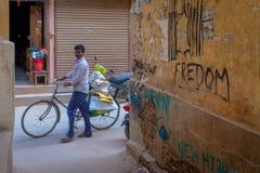 Человек непальца индийский нажимая его велосипед стоковые изображения rf
