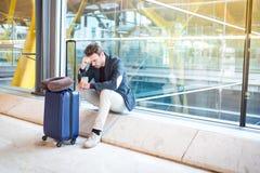 Человек несчастный и разочарованный на авиапорте его полет cancelle стоковое фото