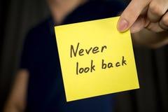 Человек не держит желтую надпись стикера никогда для того чтобы посмотреть назад стоковое фото