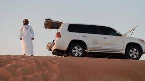 Человек низкой угловой съемки аравийский готовит виллис на верхней части дюны сток-видео