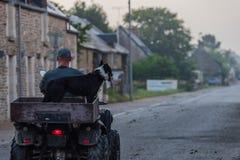 Человек нося его собаку на квадрацикле стоковая фотография